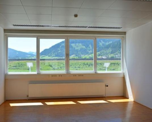 Büroraum mit großen Fenstern und Blick ins Grüne