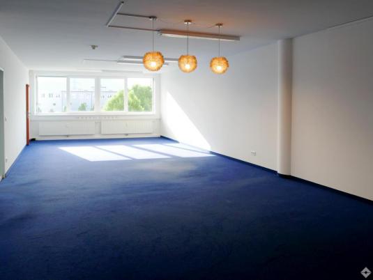 Leerer Büroraum mit Teppichboden und Deckenbeleuchtung