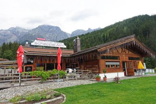 Ansicht einer klassischen Skihütte vor Bergkulisse