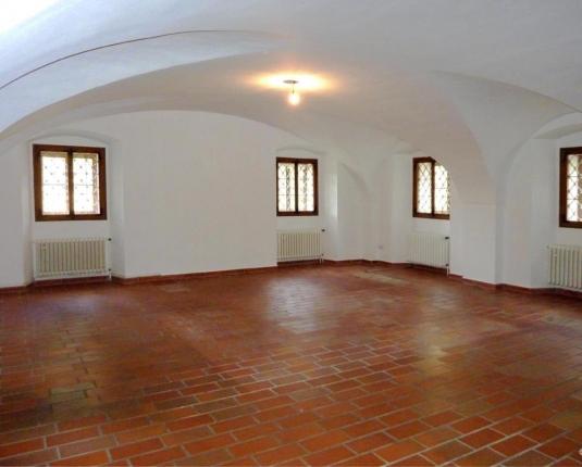 Großzügiger Raum mit Steinboden und Gewölbedecken