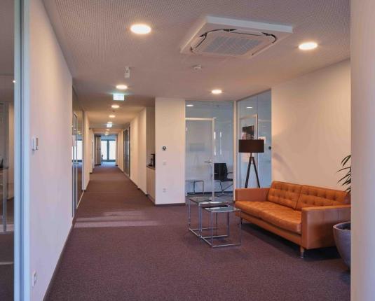 Moderner Büroflur mit Sitzgelegenheit und Glaselementen