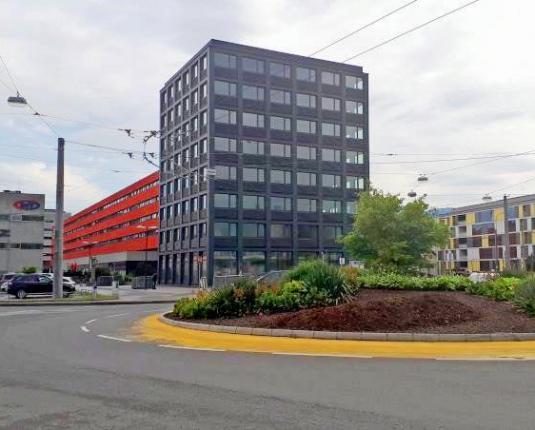 Ansicht eines modernen Büroturms mit Kreisverkehr im Vordergrund