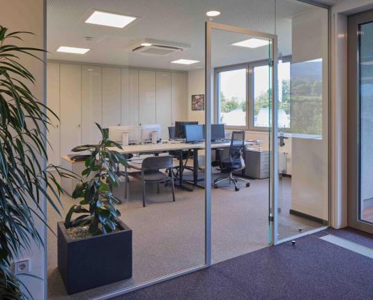 Bürobereich mit mehreren Arbeitsplätzen mit Glastrennwand